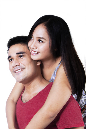 Portrait of smiling couple embracing on white background photo