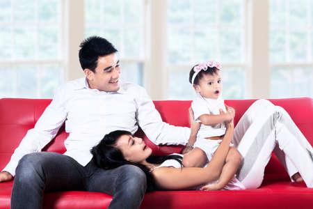 mann couch: Mama, Papa und Tochter, die Spa� auf rotem Sofa zu Hause