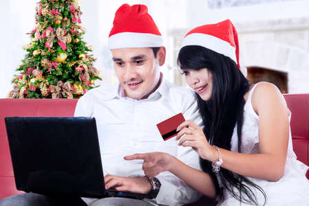 Romantic couple buying christmas gift online with laptop at home photo