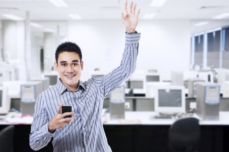 Successful businessman holding a smartphone in office photo