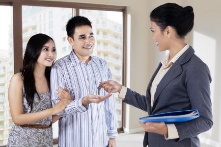不動産業者の若いカップルに新しい家の鍵を引き渡す