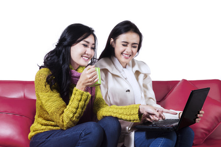 red sofa: Two winter women using a laptop together, sitting on red sofa