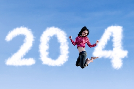 filipino: Happy asian woman is jumping with new year 2014 on blue sky