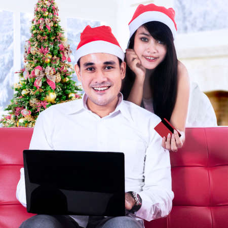 Young couple in santa hats using credit card to shopping online photo