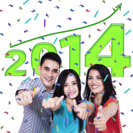 Happy young people showing thumb up in celebration new year photo