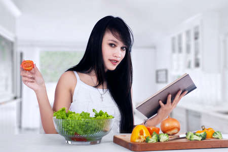 Young woman reading recipe cooking book preparing salad in the kitchen photo