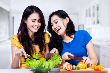 Young asian women prepare salad together in the kitchen photo