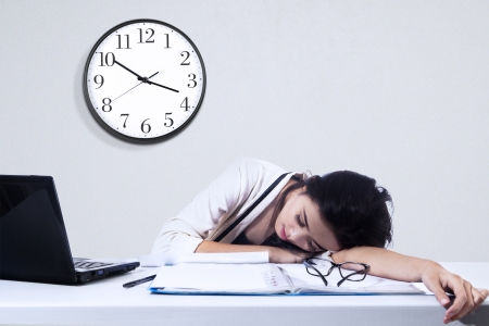 cansancio: Empresaria que duerme con la computadora portátil en el escritorio en la oficina