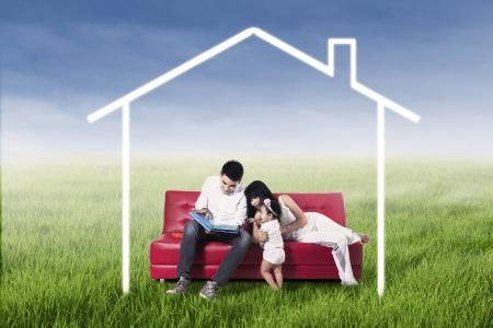 zakelijk: Het gelukkige familie ontspannen op de bank, omringd door thuis tekening in weide