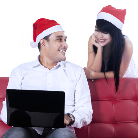 Happy christmas couple using laptop to christmas shopping online, isolated on white photo
