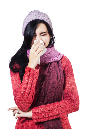 Woman dressed in winter clothing holding a tissue to her nose in a cold and flu health concept photo