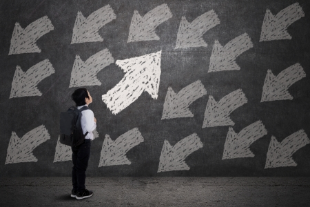 unknowing: Little boy carrying backpack, looking at arrows on blackboard Stock Photo