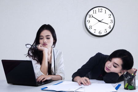 Team of two tired businesswoman because overworked in office photo