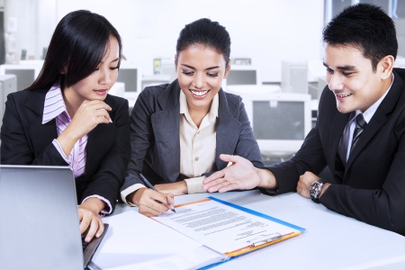 Portrait of three business partners discussing documents at meeting