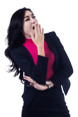 somnolent: Tired business woman yawning with her hand to her mouth and apathetic eyes Stock Photo