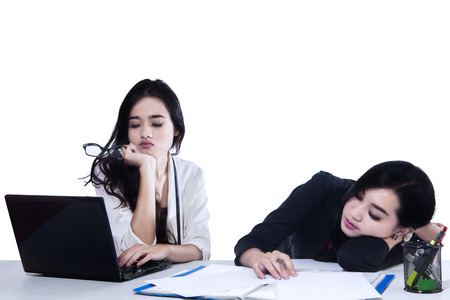 Two businesswoman tired with a laptop. Isolated on white background photo