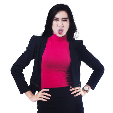 sticking: Portrait of businesswoman sticking out tongue isolated over white background