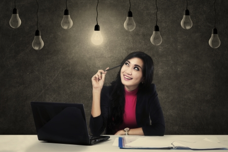 A happy business woman with light bulbs and a laptop Stock Photo - 24285793