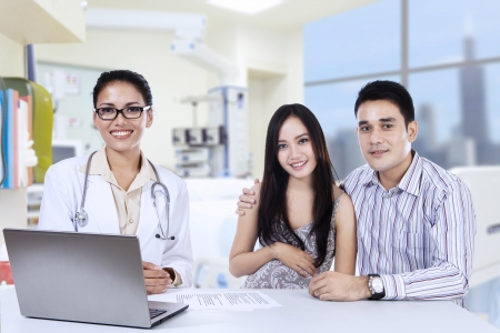 A female doctor with laptop and happy asian couple in doctors office photo