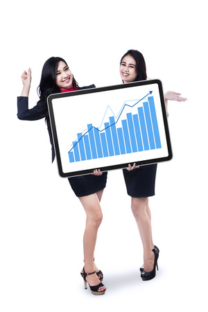 present presentation: Two happy businesswoman holding board with graph. Isolated on white Stock Photo