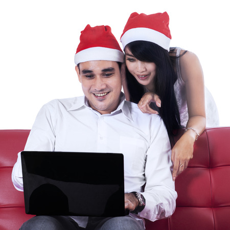 Happy christmas couple with a laptop. Isolated on white background photo