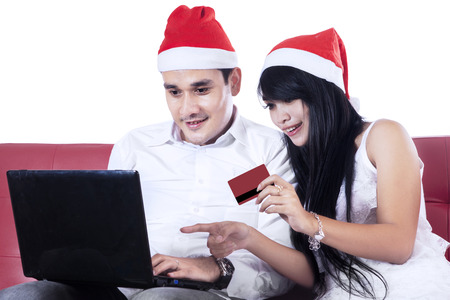 Happy couple buying a christmas gift online with laptop computer photo