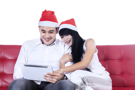 Happy young couple with digital tablet sitting on red sofa photo