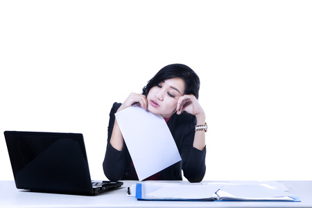 overworking: Tired business woman while using computer at desk. Isolated on white background