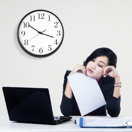 unhappy worker: Tired young businesswoman looking at laptop computer in office Stock Photo