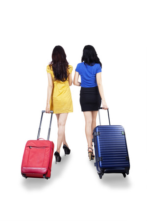 leaving: Back view of two young women traveling with suitcase.