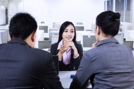 Two business people having job interview with young woman photo
