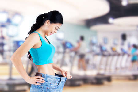 Happy woman showing her weight loss with old jeans, shot in fitness center Stock Photo - 24285893