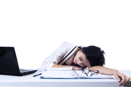 Tired young business woman asleep at desk. Isolated on white background photo