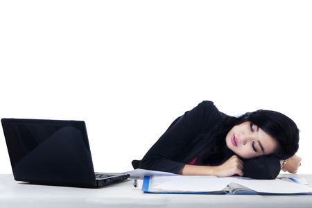 Tired young business woman sleeping next to his laptop at the desk, isolated on white photo