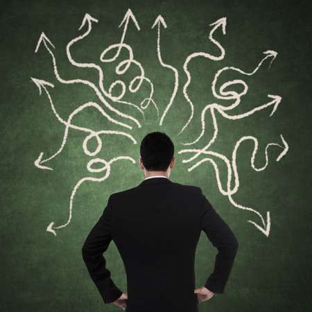 dudando: Businessman looking at arrows pointed in different directions