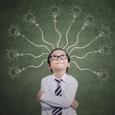 smart boy: Smart boy thinking with many ideas on the classroom Stock Photo