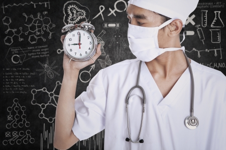 A male doctor holding alarm clock on blackboard photo