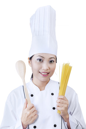Young chef holding a bunch of crude spaghetti. isolated on white background photo
