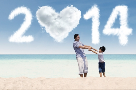 Father and his son enjoying new year holiday at beach photo