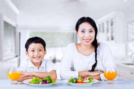 indonesian food: Portrait of happy mother and son having salad in the kitchen Stock Photo
