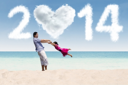 Father and daughter celebrate new year at beach photo