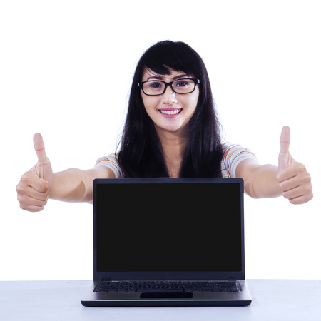 Portrait of happy college student giving thumbs up with copyspace on laptop photo