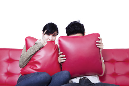 Couple scared sitting on red sofa and watching horror movie photo