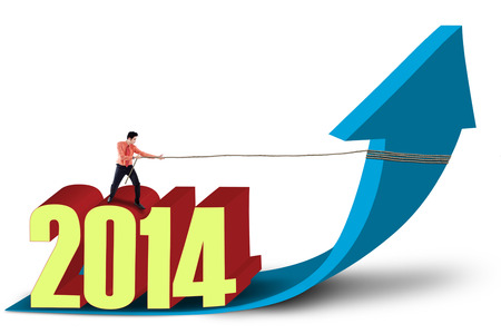 growth enhancement: Young businessman is pulling the new year 2014 with chain isolated on white background