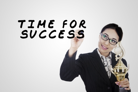 Business woman writing text of time for success in a glass board photo