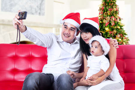 Smiling family in santa hats taking picture with camera  photo