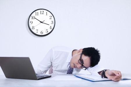 exhausted: Tired businessman sleeping on a laptop with clock in the office