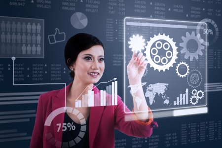 Businesswoman controls the business by using gears in a virtual system Stock Photo
