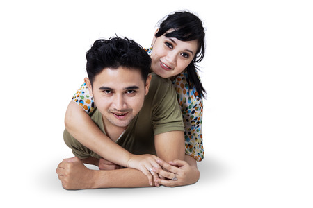 Happy young couple lying down on the floor, isolated on white background photo