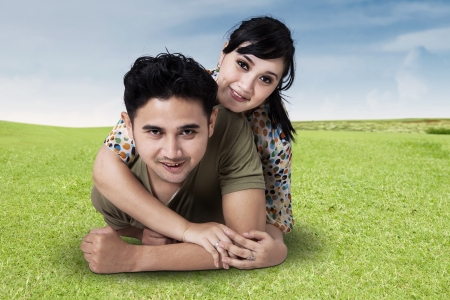 Portrait of a happy hispanic young couple lying on grass in a park photo